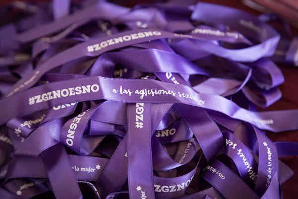 Pulseras moradas con el lema de la campaña '#ZGZNOesNO'